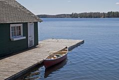Canoe on lake docked by boat house Royalty Free Stock Image