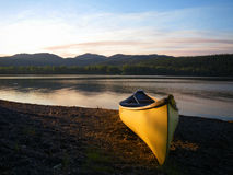 Canoe on lake shore at dusk. Royalty Free Stock Image