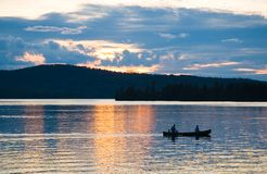 Canoe on lake at sunset. A couple out for a romantic sunset canoe trip across Moosehead Lake, Maine, on a warm summer evening royalty free stock photography