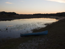 Canoe By the Lake At Sunset. A canoe on shore by a lake during the evening sunset Royalty Free Stock Photos