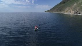 Canoe in the lake. Tourist canoeing on the Bay. Aerial drone shot. Canoe on the lake. Tourist woman canoeing on the Bay. Aerial drone shot 4K. Drone folow the stock footage