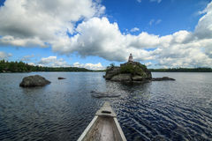 Canoe and light house on Canadian lake. Wide angle view of a canoe approaching a small light house on rock in tranquil lake.The sky is blue with white fluffy Royalty Free Stock Photos