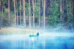 Canoe on misty forest pond Royalty Free Stock Images