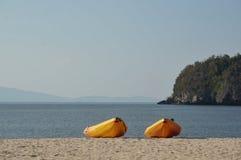 Canoe na praia e nas rochas do oceano no fundo fotos de stock royalty free