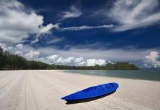 Canoe na praia em um céu azul claro fotografia de stock royalty free