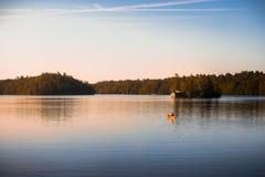 Canoe no lago tranquilo Joseph, Muskoka, no nascer do sol imagem de stock royalty free