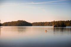 Canoe no lago tranquilo Joseph, Muskoka, no nascer do sol imagens de stock royalty free