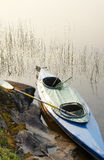 Canoe with oar and fishing-tackle in Wilderness. Canoe with oar and fishing-tackle rests on shore of lake in summer Royalty Free Stock Photo