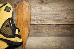 Canoe paddle and life jacket. Paddling concept - canoe paddle and life jacket against weathered wood with a copy space Stock Images
