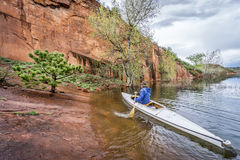 Canoe paddler and sandstone cliff. Paddler in an decked expedition canoe approaching rocky sandstone shore - Horsetooth Reservoir near Fort Collins, Colorado Royalty Free Stock Image