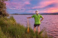Canoe paddler and sunset sky. Male canoe paddler watching pink sunset sky over a lake and Front Range of Rocky Mountains Royalty Free Stock Photography