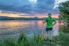 Canoe paddler watching sunset. Over Rocky Mountains from a lake shore in Colorado near Loveland Royalty Free Stock Images