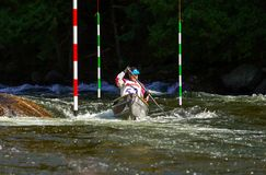 Canoe paddler in a whitewater slalom race. Unidentified paddler steering his canoe through the slalom gates and rapids on Gull River in Minden Royalty Free Stock Image