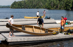 Canoe paddlers leaving on a trip. Group of outdoor enthusiasts preparing their canoes and camping gear for an overnight trip in Algonquin Park interior Royalty Free Stock Photos