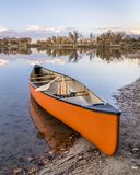Canoe with paddles on a lake shore royalty free stock images