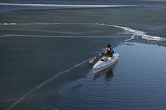 Canoe paddling on ice covered lake Stock Image