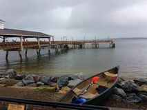 Canoe and Pier. Kayak with Oar Overlooking Rocks and Ocean at Fishing Pier on St. Simons Island, GA on Cloudy Day Royalty Free Stock Image