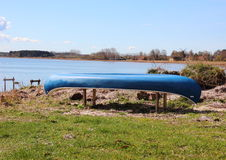 Canoe placed at beach with blue sky and water front Stock Images