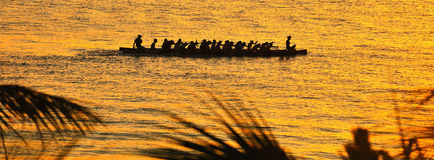 The canoe queen. A silhouette of a large war canoe at sunset being rowed by strong men with a young girl sitting crossed legged on the prow Royalty Free Stock Images