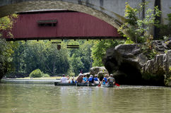 Canoe rides under the covered bridge Royalty Free Stock Images
