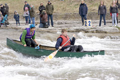 Canoe in River Race - Port Hope, March 31, 2012. Participants paddle a canoe through the Ganaraska River rapids on March 31, 2012 in Port Hope, Ontario. The Royalty Free Stock Image