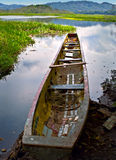 Canoe at Rivers Edge, Panama. A long tattered empty canoe sits at the glassy waters edge in the Panama Jungle near Rio Chagres (Chagres River) close to the Stock Image