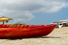 Canoe on the sand. A red canoe on the sand during a sunny day Stock Photo