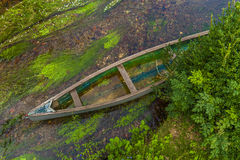Canoe in shallow river. Antique canoe in shallow river as seen from above Stock Image