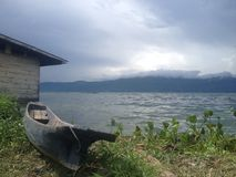 Canoe on the shore of lake Toba. Lake Toba is the biggest volcanic lake in the world. Located on Sumatra, Indonesia, within the crater of an extinct super Stock Photo