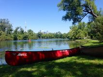 Canoe on shore on Toronto Islands with city skyline behind. A red canoe sits on shore in a picnic area on the Toronto Islands with the city skyline and other Royalty Free Stock Photos
