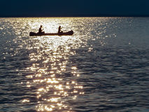 Canoe Silhouette - Sparkling Golden Ribbon Setting Sun Royalty Free Stock Image