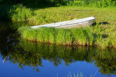 Canoe sitting along the blue waters of a river. Royalty Free Stock Photography