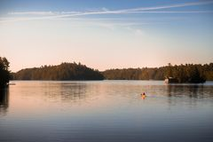 Canoe on tranquil Lake Joseph, Muskoka, at sunrise. stock photography