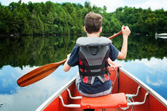 Canoe trip. Child in the front of a canoe paddling on a calm Canadian lake Royalty Free Stock Photo