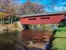 Canoe Trip Passing Underneath Old Covered Bridge On Sunny Autumn Day. Groups of people in canoes paddling down stream through beautiful autumn countryside stock photography