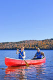 Canoe trip on scenic lake in fall royalty free stock images