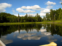 Canoe view. Wonderous sky reflection while drifting in canoe on Penassi Lake, Northern Ontario Royalty Free Stock Image