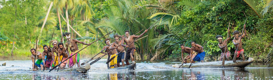Canoe war ceremony of Asmat. INDONESIA, IRIAN JAYA, ASMAT PROVINCE, JOW VILLAGE - MAY 23: Canoe war ceremony of Asmat people. Headhunters of a tribe of Asmat Stock Image