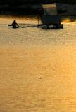 Canoeing на заходе солнца Стоковое Фото