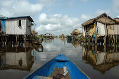 Canoeing through African village royalty free stock images