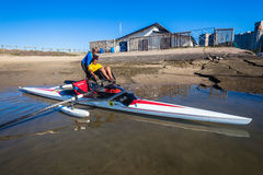 Canoeing Assist Handicap Girl. Girl handicapped rowing modified skull single skull canoe with flotation buoys each side with her coach assistance at Durban Stock Photography