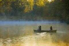 Canoeing através da névoa da manhã Imagens de Stock
