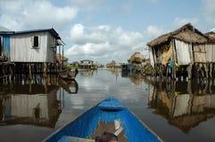 Canoeing através da vila africana Imagens de Stock Royalty Free