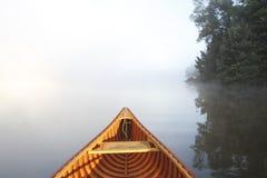 Canoeing auf einem nebelhaften See lizenzfreies stockbild