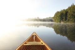 Canoeing auf einem nebelhaften See Stockfotos