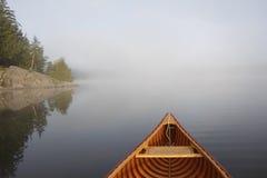 Canoeing auf einem nebelhaften See Lizenzfreie Stockfotografie