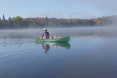Canoeing on an Autumn Lake Stock Photography