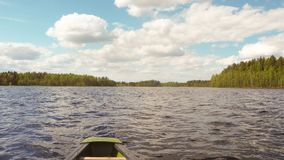 Canoeing at finnish lake in summer. Canoeing at beautiful finnish lakescape in summer stock photo