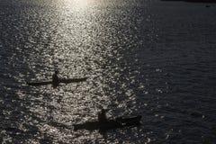 Canoeing bij zonsondergang Stock Foto's