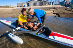 Canoeing Coach Handicap Girl. Girl handicapped rowing modified skull single skull canoe with flotation buoys each side with her coach assistance at Durban Rowing Stock Photos